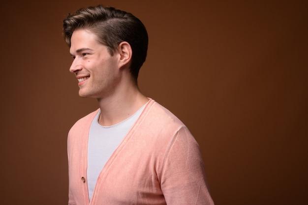 Studio shot van de jonge knappe man tegen bruine achtergrond