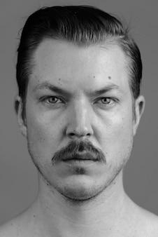Studio shot van de jonge knappe scandinavische man met snor shirtless tegen grijs in zwart-wit