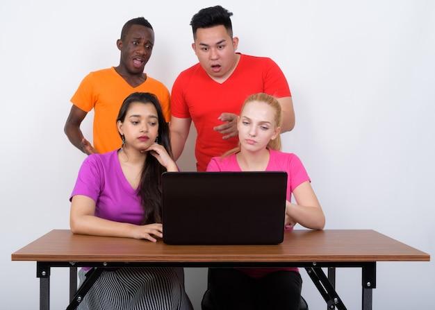 Studio shot van diverse groep multi-etnische vrienden met behulp van laptop