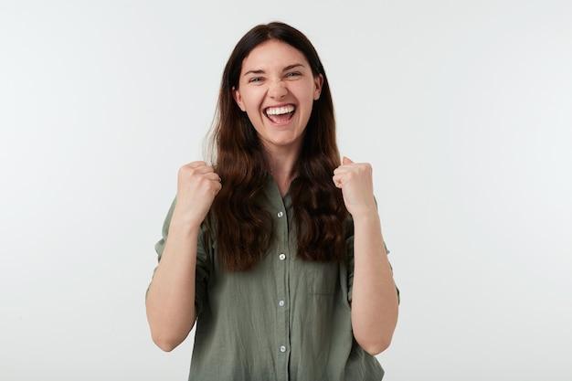 Studio shot van dolblij jonge aantrekkelijke brunette vrouw met losse haren verhogen handen in ja gebaar