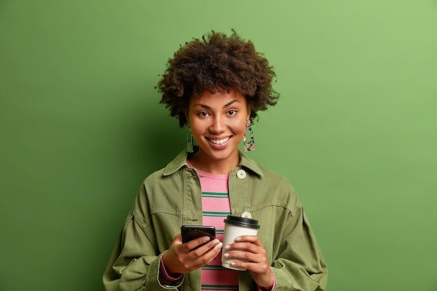 Studio shot van donkere huid jonge vrouw houdt mobiele telefoon en koffie te halen