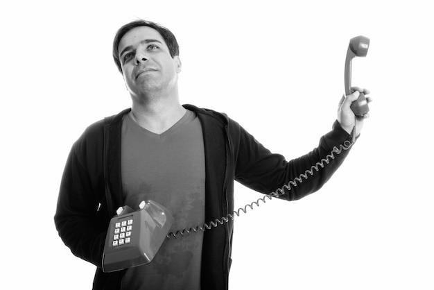 Studio shot van doordachte jonge perzische man die oude telefoon weghoudt terwijl hij geïrriteerd kijkt