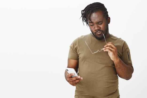 Studio shot van doordachte man met bril poseren tegen de witte muur met zijn telefoon