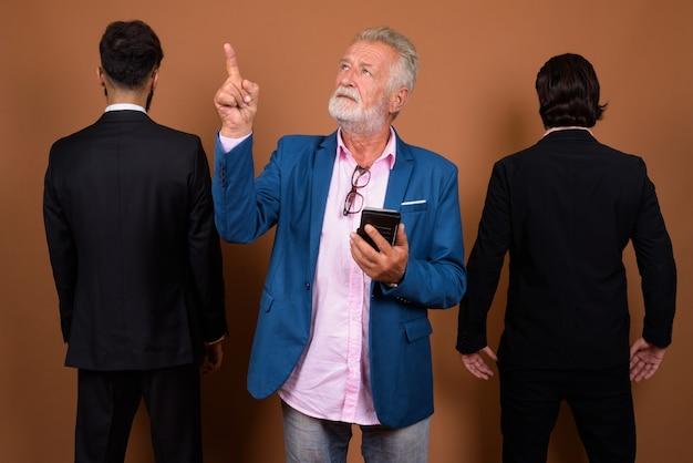 Studio shot van drie multi-etnische bebaarde zakenlieden samen tegen bruine achtergrond