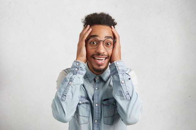 Studio shot van een donkere bebaarde man draagt een casual shirt, drukt schok en opwinding uit,