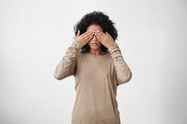 Studio shot van een donkere jonge vrouw met zwart krullend haar dat de ogen bedekt
