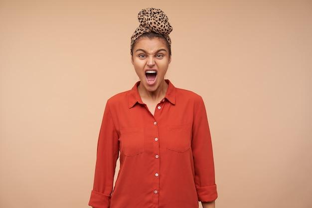 Studio shot van een gekke jonge mooie brunette vrouw die boos schreeuwt terwijl ze naar de voorkant kijkt, haar handen langs het lichaam houdt terwijl ze over beige muur staat