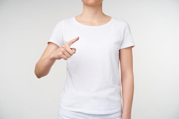 Studio shot van een jonge blonde vrouw die opzij toont met wijsvinger terwijl ze woord u / hij op gebarentaal betekent, geïsoleerd op witte achtergrond