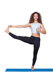 Studio shot van een jonge fitte vrouw die yoga-oefeningen doet.