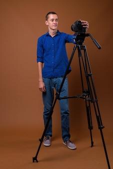 Studio shot van een jonge man op bruin