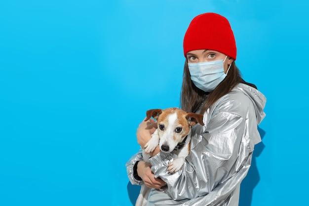 Studio shot van een jonge vrouw in een rode hoed en een zilveren jasje met medische gezichtsmasker staande samen met haar hond geïsoleerd op blauwe achtergrond. coronavirus, covid 19, zorgconcept