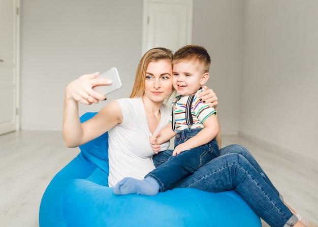 Studio shot van een moeder die haar kind vasthoudt en een selfie op smartphone neemt