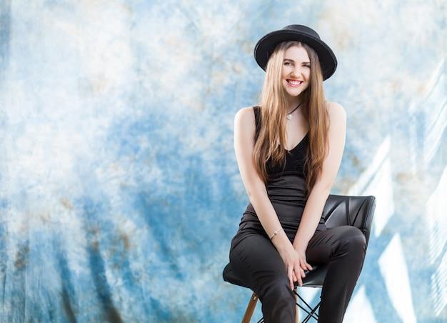Studio shot van een prachtige jonge vrouw in elegante zwarte kleding en klassieke hoed.