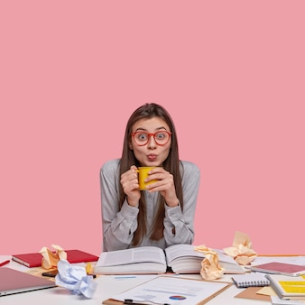 Studio shot van emotionele mooie vrouw met lang steil haar, maakt grimas, drinkt thee, bereidt zich voor op lezing