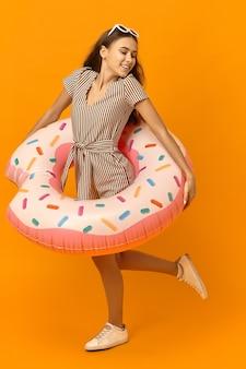 Studio shot van energieke levendige jonge vrouw in tinten, gestreepte jurk en sneakers met plezier