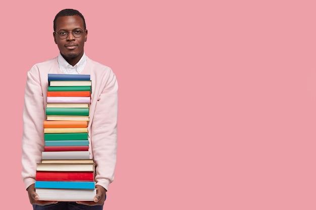 Studio shot van ernstige donkere huid mannelijke student draagt enorme stapel boeken, leest en propt voor toelatingsexamen