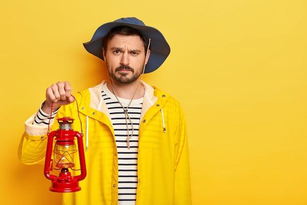 Studio shot van ernstige ontevredenheid man heeft kleine baard en snor, klaar om een nieuwe plek in de duisternis te ontdekken, houdt petroleumlamp vast, gekleed in regenjas en heagear.
