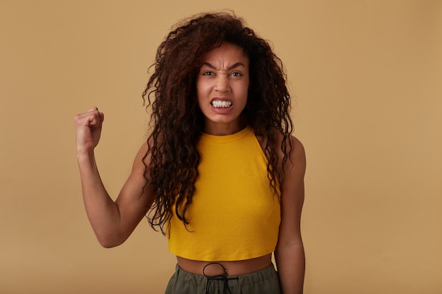 Studio shot van geïrriteerde lang krullende donkere huid vrouw grimassen haar gezicht terwijl ze boos naar de camera kijkt, haar hand omhoog houden terwijl ze op beige achtergrond staat