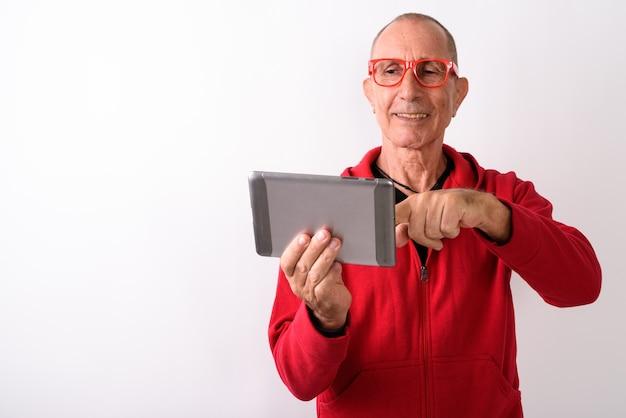 Studio shot van gelukkig kale senior man glimlachend en met behulp van digitale tablet