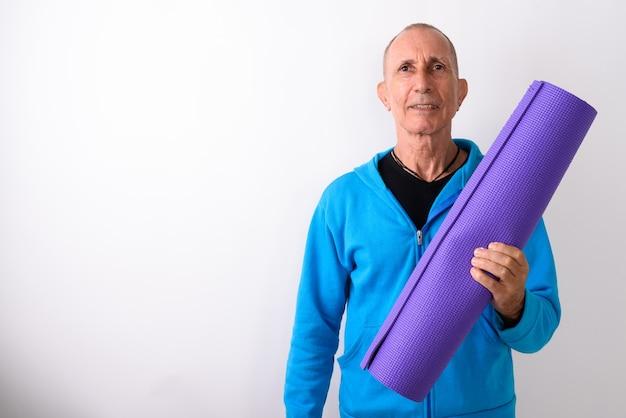 Studio shot van gelukkig kale senior man glimlachend terwijl yoga mat