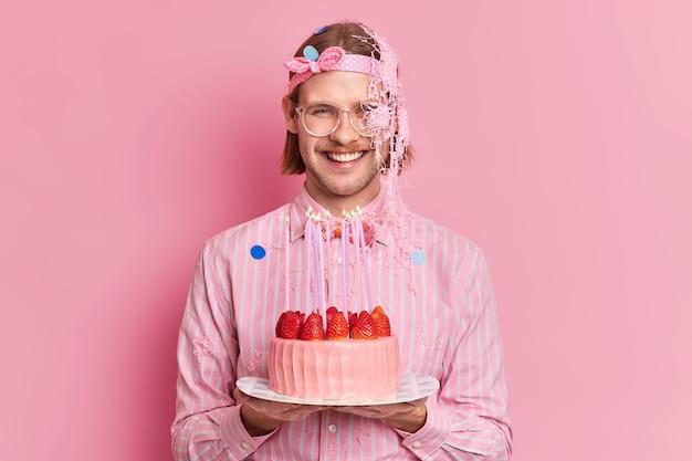 Studio shot van gelukkig man viert verjaardag houdt smakelijke aardbeientaart ontmoet gasten dresed in feestelijke kleding geïsoleerd op roze achtergrond