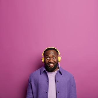 Studio shot van gelukkig ongeschoren man luistert audiotrack in koptelefoon, kijkt boven met glimlach, gekleed in paars shirt, heeft een gezonde donkere huid