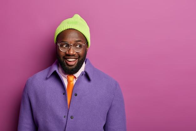 Studio shot van gelukkig zwarte afro-amerikaanse man kijkt graag opzij, draagt stijlvolle paarse jas, hoed en optische bril, drukt oprechte emoties uit