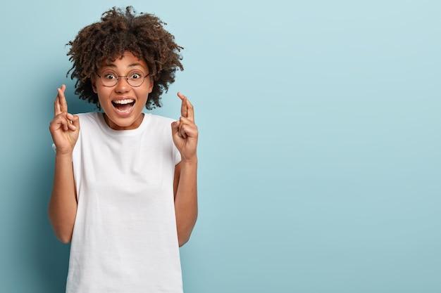 Studio shot van gelukkige donkere huid vrouw kruist vingers voor geluk
