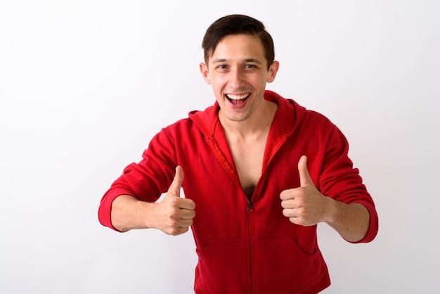 Studio shot van gelukkige jonge knappe man die lacht terwijl het geven van do