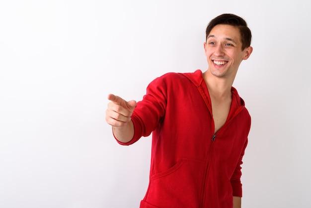 Studio shot van gelukkige jonge knappe man glimlachend terwijl t wijzen