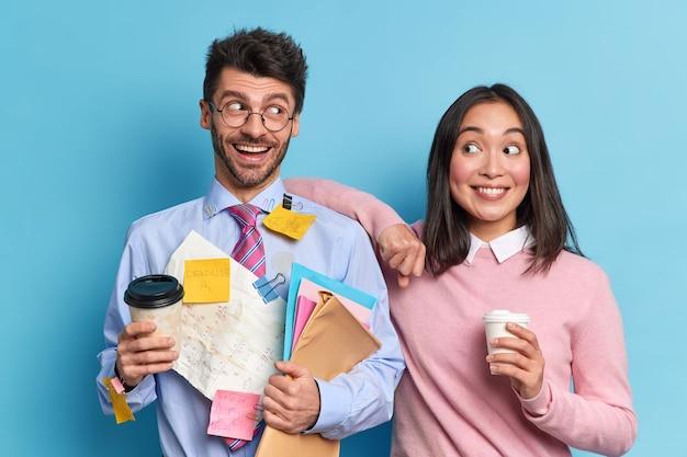 Studio shot van gelukkige klasgenoten bespreken schoolprojectideeën staan blij drankje afhaalmaaltijden koffie kijken elkaar vrolijk aan. blij nerd man houdt mappen bedekt met stickers op formeel overhemd