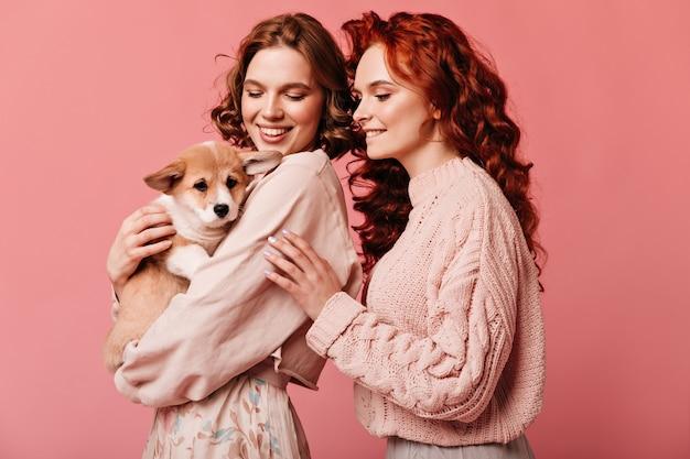 Studio shot van gelukkige meisjes spelen met schattige hond. lachen blanke dames poseren met huisdier op roze achtergrond.
