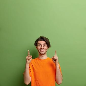 Studio shot van gelukkige ongeschoren europese man met positieve uitdrukking wijst naar boven op lege ruimte
