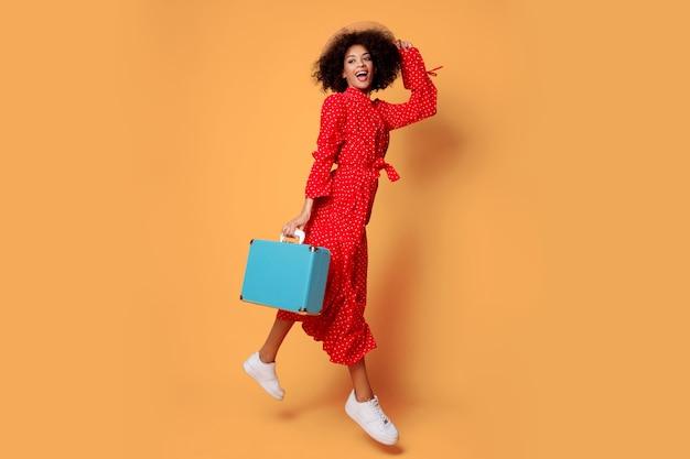 Studio shot van gelukkige speelse zwarte vrouw gek rond en springen op oranje