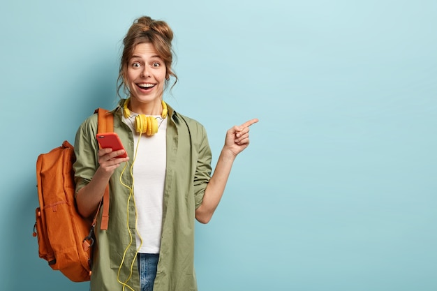Studio shot van gelukkige tienermeisje houdt mobiele telefoon, controleert e-mail, krijgt nieuwe melding, gebruikt moderne koptelefoons, wijst naar kopie ruimte voor merknaam of label, draagt losse kaki shirt, draagtas