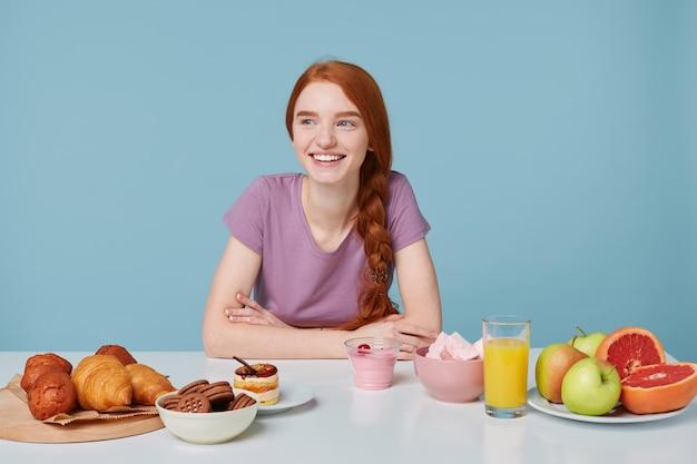 Studio shot van glimlachend roodharig meisje met gevlochten haar zittend aan een tafel, op het punt om te lunchen op zoek naar linkerkant