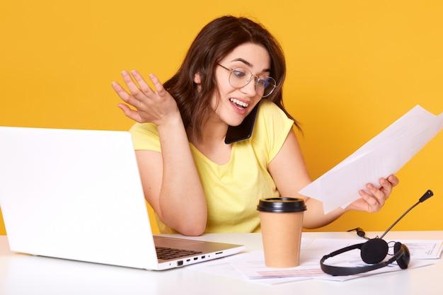 Studio shot van glimlachende vrouw kijken naar documenten in haar hand tijdens het praten aan de telefoon met haar zakenpartner, zit aan haar bureau