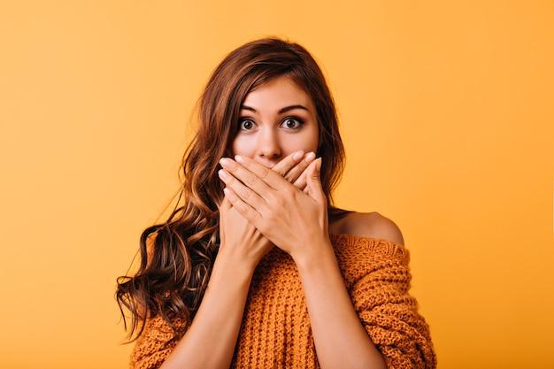 Studio shot van grappig verbaasd meisje met lang glanzend haar. indoor portret van verrast verlegen dame geïsoleerd op geel.