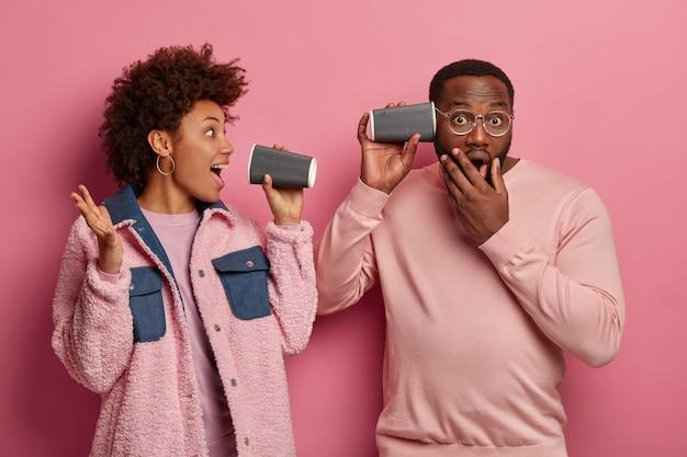 Studio shot van grappig verrast afro-amerikaanse vrouw en haar vriendje spelen met papieren wegwerpbekers na het drinken van koffie, veel plezier samen