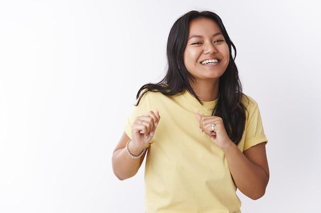 Studio shot van grappige en enthousiaste vrolijke vrolijke vrouw in geel t-shirt die dansbewegingen maakt, lichaam en handen schuddend, bijwonend geweldig feest met coole muziek op witte achtergrond