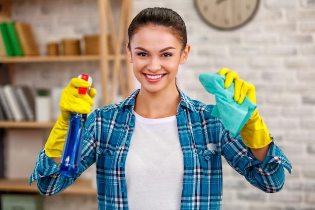 Studio shot van huishoudster. mooie vrouw schoonmaak kamer. vrouw die handschoenen draagt, glimlacht en een fles met ontsmettingsmiddel vasthoudt