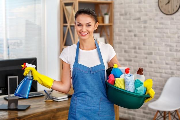 Studio shot van huishoudster. mooie vrouw schoonmaak kantoor. vrouw die handschoenen draagt, glimlacht en een kom vol flessen met ontsmettingsmiddel vasthoudt