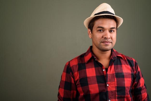 Studio shot van indiase toeristische man met hoed en rood geruit overhemd tegen gekleurde achtergrond