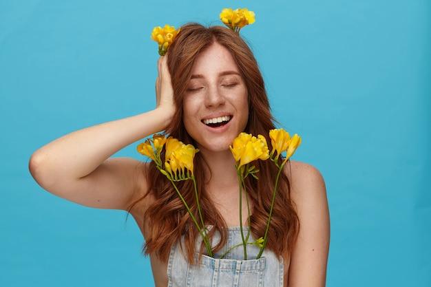 Studio shot van jonge aangenaam uitziende foxy vrouw in spijkerbroek top met opgeheven palm op haar hoofd en vrolijk lachend met gesloten ogen, staande op blauwe achtergrond