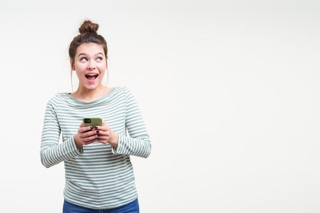 Studio shot van jonge aantrekkelijke geagiteerde brunette vrouw met broodje kapsel mobiele telefoon in opgeheven handen houden en emotioneel opzij kijken met brede mond geopend, geïsoleerd over witte muur