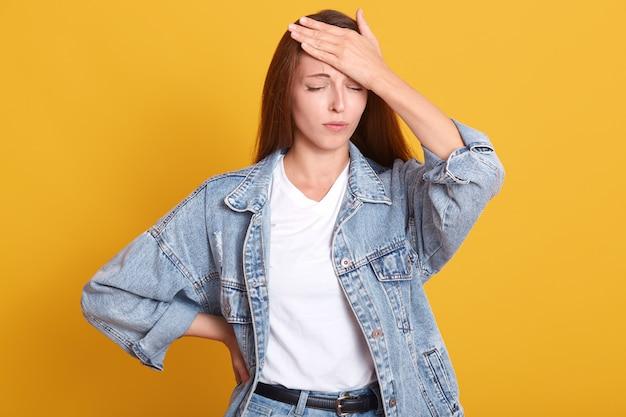 Studio shot van jonge aantrekkelijke vrouw geïsoleerd op gele studio achtergrond staan met de hand op het voorhoofd, herinnert zich voor fout of iets belangrijks.