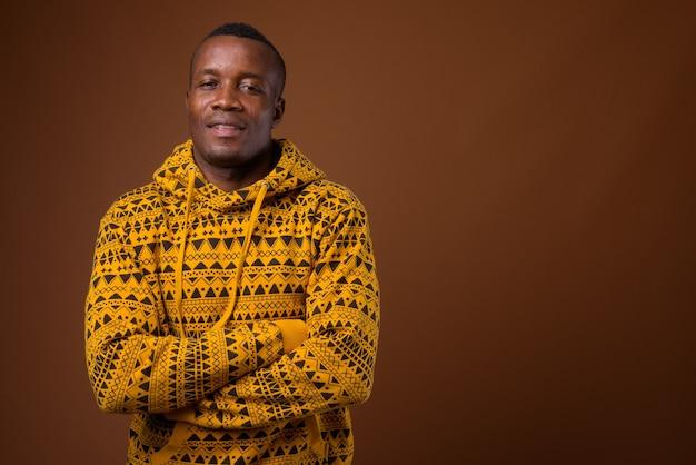 Studio shot van jonge afrikaanse man tegen bruine achtergrond