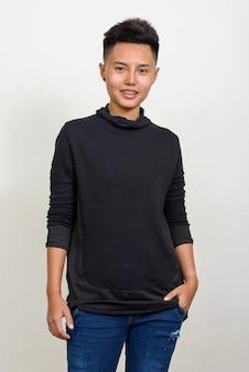 Studio shot van jonge aziatische lesbische vrouw met kort haar tegen een witte achtergrond