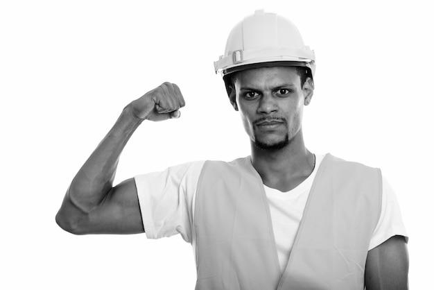 Studio shot van jonge bebaarde afrikaanse man bouwvakker geïsoleerd tegen een witte achtergrond in zwart-wit