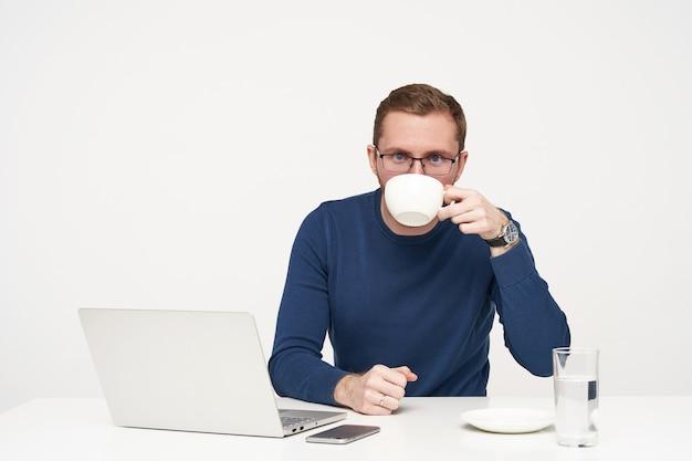 Studio shot van jonge bebaarde man in glazen met koffiepauze tijdens het werken met zijn laptop en camera kijken, gekleed in blauwe trui zittend op witte achtergrond